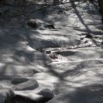 Stream surrounded by snow and ice