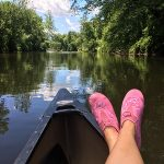Crossed human legs with pink shoes up against the bow of a canoe in foreground, with river and green trees in background