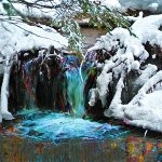 Small waterfall surrounded by snow-covered ground