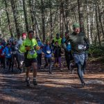 A large group of people running on the trail at the Chesterfield Gorge, wearing race bibs and dressed warmly. Sunlight shining through trees in the background.