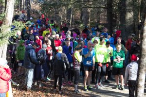 Crowd of runners dressed warmly, standing on a trail with trees in background