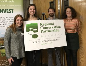 Brigid and three students pose behind a Regional Conservation Partnership Network Gathering sign