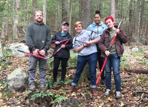 Five college students pose with tools in the woods.