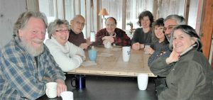 Eight people sitting around a table with mugs of hot beverages pose for a picture by smiling at the camera