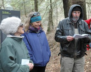 A man reads poetry in the forest while two women listen.