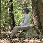 person siting on rock in woods