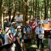 Eric, standing to the right in a wooded area, holding up a binder and pointing out an image, while a crowd looks on.