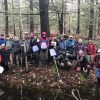 A couple dozen people pose for a photo in the woods behind a vernal pool