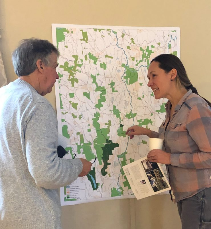 Two people in discussion, in front of a map