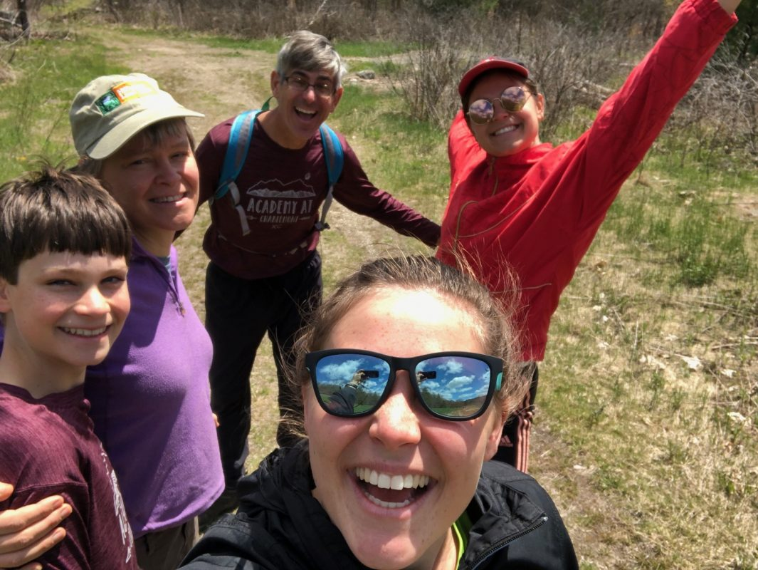Sally Loomis, her husband, and three kids pose for a fun selfie on a hike
