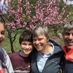 Sally, her husband, and two of her kids in front of a tree with pink blossoms on a recent hike