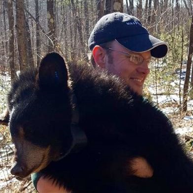 Andrew Madden in the woods, holding a black bear cub
