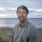 Rob Warren, smiling into the camera, with a beach and water in the background