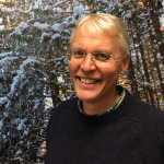 Paul Wetzel, smiling into the camera, standing in front of an image of snow-covered trees